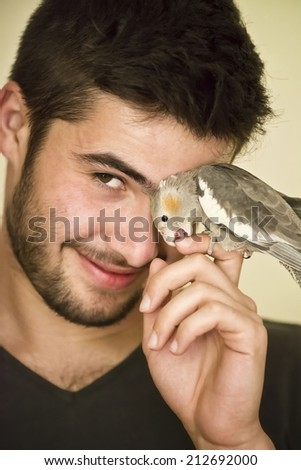 Attractive man playing with his parrot indoors  - stock photo