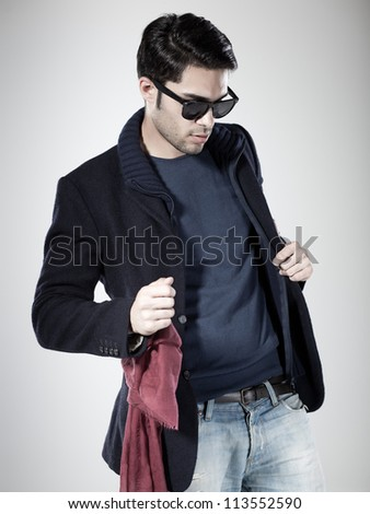 attractive man posing in the studio wearing sunglasses - stock photo