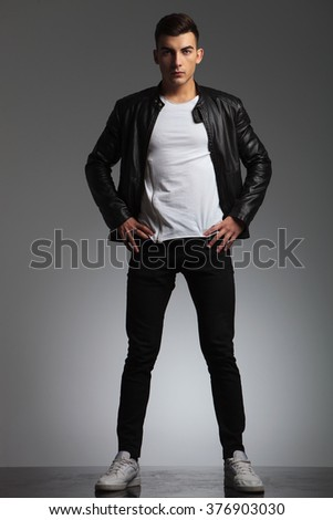 attractive man posing spread legs and hands on waist while wearing black leather jacket and looking at the camera in studio background