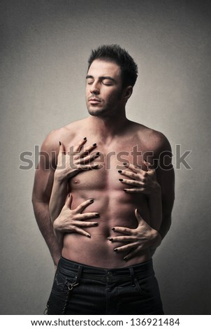 attractive man shirtless with women's hands on the torso - stock photo