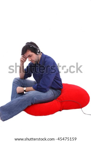 Attractive man sitting on a big heart pillow and listen to music