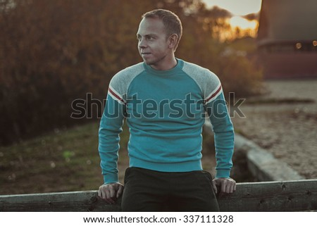 Attractive man sitting on  beach in the evening sunset after sport.