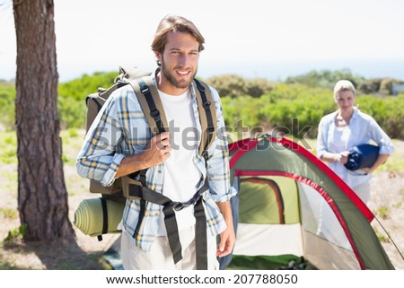 Attractive man smiling at camera while partner pitches tent on a sunny day - stock photo