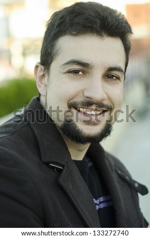 Attractive man smiling outdoors. Appearance Latin or Arabic. - stock photo
