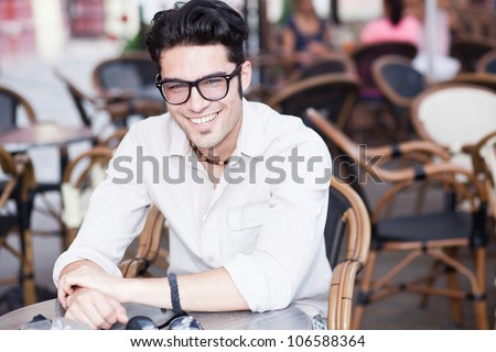 attractive man smiling wearing glasses standing at a terrace - stock photo