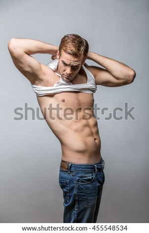 Attractive man taking off a white singlet while standing in the studio on the gray background. His hands are behind the head. Guy wears blue jeans. Vertical. - stock photo