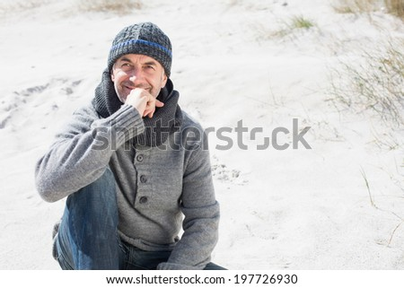 Attractive man thinking on the beach in hat and scarf on a bright but cool day - stock photo
