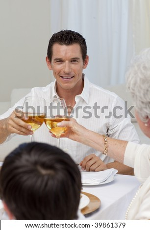 Attractive man toasting with his mother in a Christmas dinner