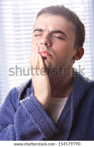 Attractive man touching his cheek with a pained expression in bathroom - stock photo