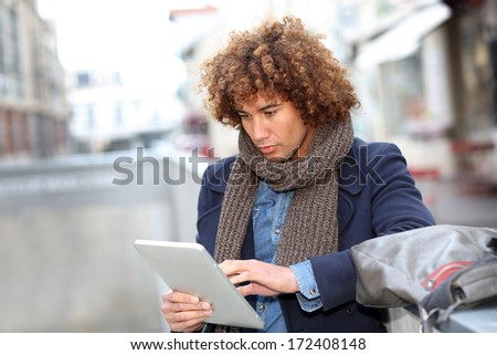 Attractive man using digital tablet in town - stock photo