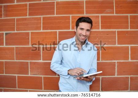 Attractive man using electronic tablet leant on brickwall - stock photo