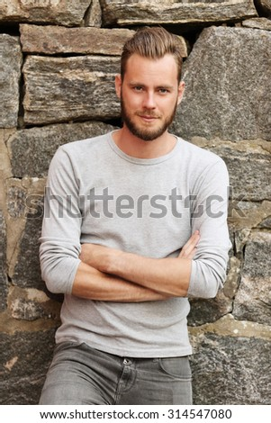 Attractive man wearing a grey sweater standing in front of a wall outside on a sunny summer day.  - stock photo
