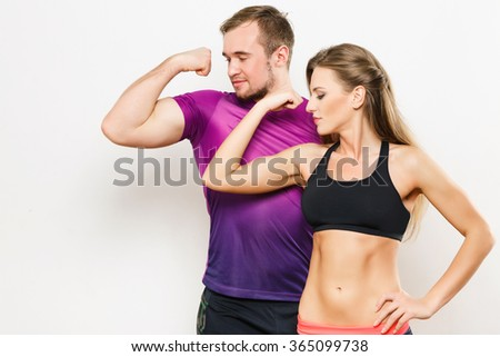 Attractive man wearing dark purple sport T-shirt and black trousers with beautiful girl in short black top showing muscles, looking at muscle, fitness, sport.