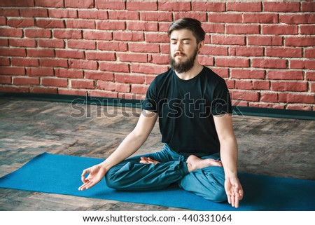 Attractive man with a beard and closed eyes wearing black T-shirt and blue trousers doing yoga position on blue matt at wall background, copy space, portrait, lotus asana, padmasana, meditation - stock photo