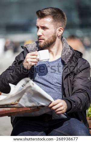 Attractive man with a beard is drinking coffee in a coffee shop