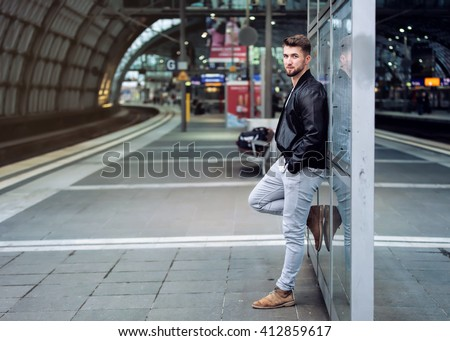 Attractive man with a beard is waiting at the train station