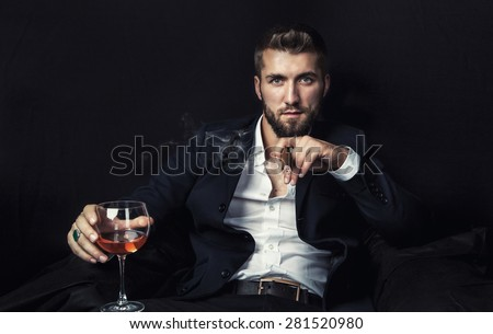 Attractive man with a cigar, and a glass of wine in his hands - stock photo