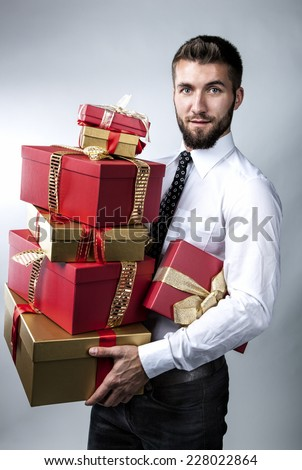 Attractive man with a lot of presents in his hands