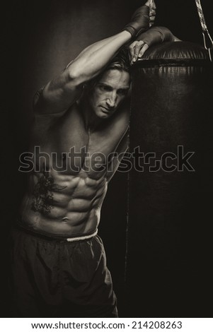 Attractive Man With Boxing Bag - A Man With A Tattoo In Red Boxing Gloves - Boxing On Black Background - The Concept Of A Healthy Lifestyle - The Idea For The Film About Boxing