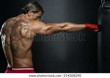Attractive Man With Boxing Bag - A Man With A Tattoo In Red Boxing Gloves - Boxing On Black Background - The Concept Of A Healthy Lifestyle - The Idea For The Film About Boxing - stock photo