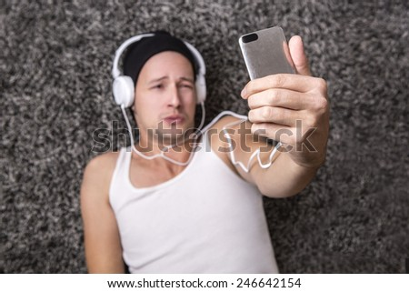 Attractive man with headphones in a white shirt unhappy to make selfie with his mobile phone - stock photo