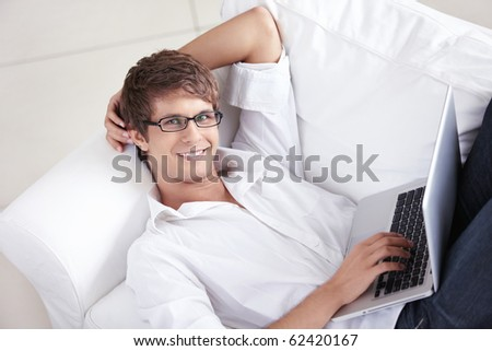 Attractive man with laptop on a couch - stock photo