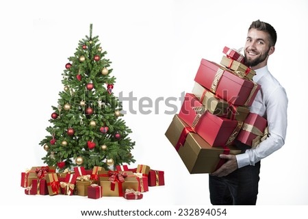 Attractive man with many present boxes and a christmas tree - stock photo