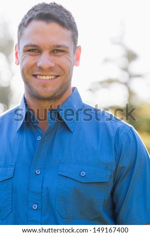 Attractive man with short hair and a blue shirt looks at the camera - stock photo