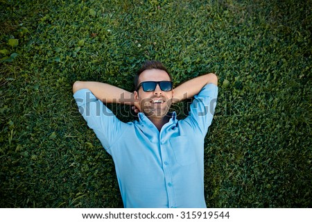 attractive man with sunglasses relaxing on the grass with his hands under the head - stock photo
