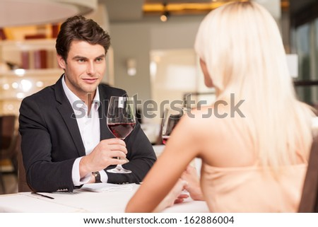 Attractive man with wine glass looking at beautiful woman. Trying to seduce  - stock photo