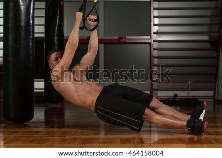 Attractive Man working out with Fitness Straps In a gym