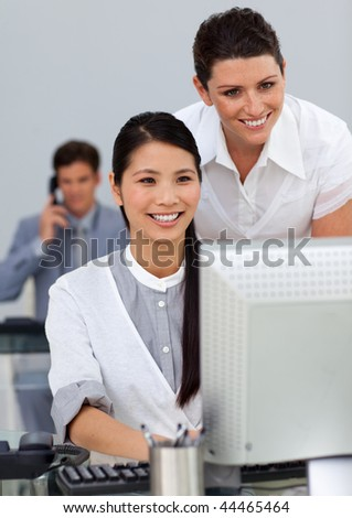 Attractive manager checking her employee's work in the office
