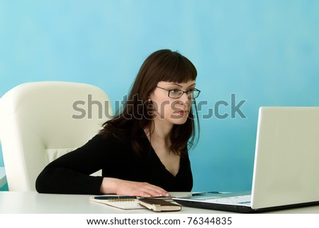Attractive manager looking at laptop in office