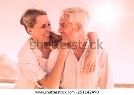 Attractive married couple hugging at the beach on a sunny day - stock photo