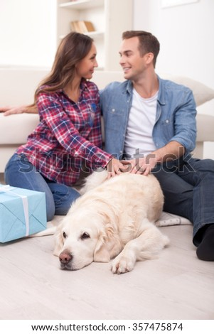Attractive married couple is sitting on flooring and embracing. The dog is lying near them. The man and woman are stroking the animal and smiling - stock photo