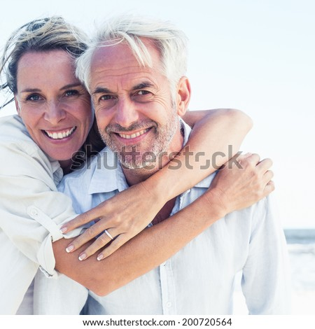 Attractive married couple posing at the beach on a sunny day