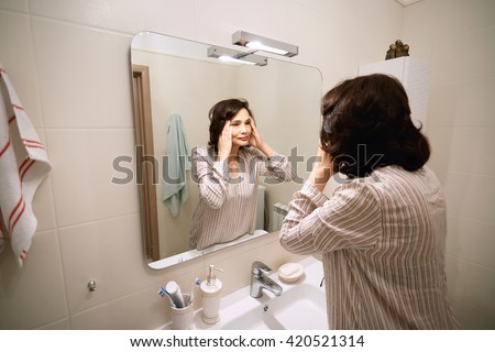 Attractive mature Asian woman with dark hair, wearing night-suit, looking at her reflection in the mirror while doing morning routine procedures in the modern bathroom.  Beauty and health concept - stock photo