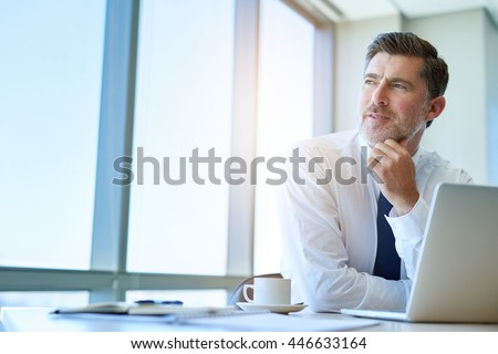 Attractive mature business executive with a stylish short beard, sitting at his office desk and looking out of his window with a thoughtful and optimistic expression - stock photo