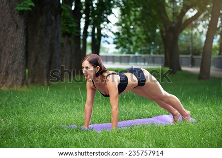 attractive mature caucasian woman in black sportswear doing plank exercises outdoor in green park - stock photo
