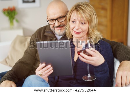 Attractive mature couple drinking wine and reading something enjoyable on their tablet computer while sitting together on sofa in living room - stock photo