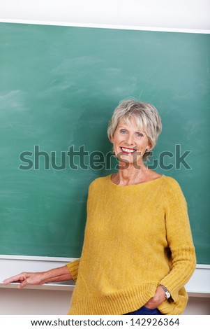 Attractive mature teacher standing in front of a blackboard - stock photo