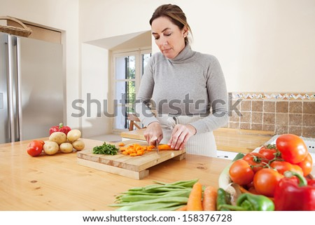 Attractive mature woman chopping herbs and carrots, and cooking vegetables in the kitchen at home, with healthy organic produce and using a knife and a wooden chopping board. - stock photo
