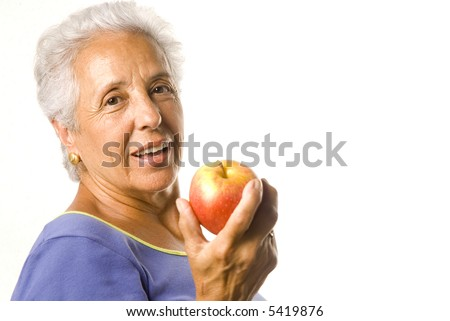 Attractive mature woman eating a red apple - stock photo
