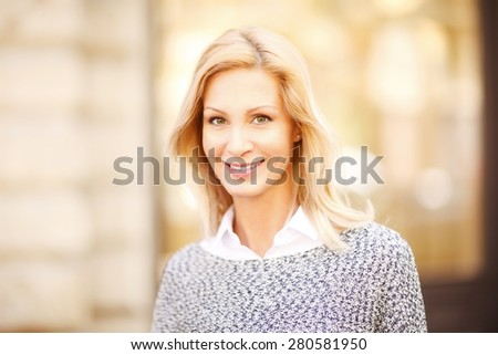 Attractive mature woman looking at camera and smiling while standing in front of shop window on the street. - stock photo