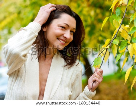 attractive mature woman outside relaxing in the park - stock photo
