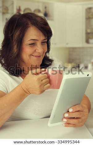 Attractive mature woman reading a book on tablet computer.