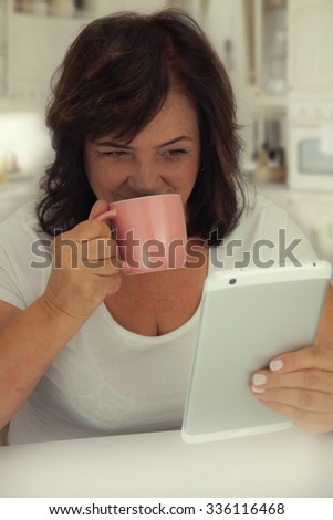 Attractive mature woman reading a book on tablet computer. - stock photo