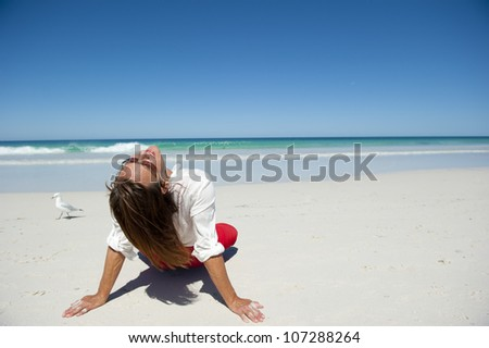 Attractive mature woman sitting in seductive pose and happy relaxed at tropical beach paradise, isolated with ocean and blue sky as background and copy space. - stock photo