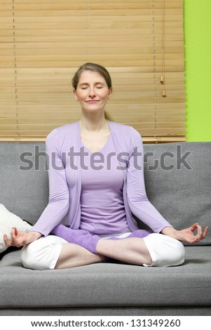 Attractive mature woman sitting in the lotus position on a couch in her living room meditating with her eyes closed and a serene expression - stock photo