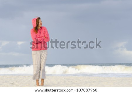 Attractive mature woman standing alone at the beach, wearing pink hooded sweater to keep warm, isolated with dark storm clouds and wild ocean as background and copy space. - stock photo